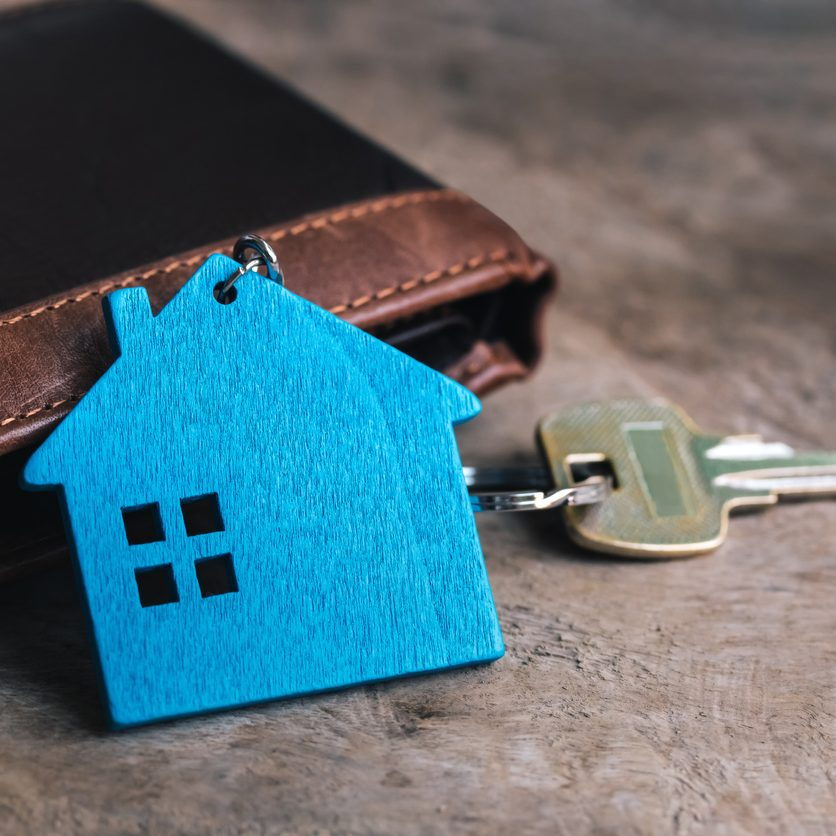 Miniature home and metal key and wallet on old wooden table. Real estate investment with new home.